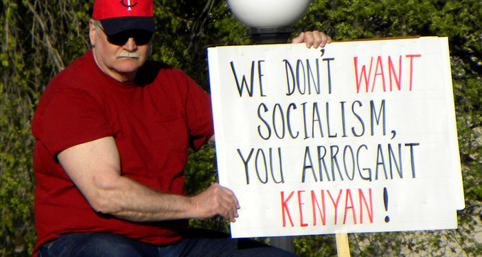 """Man holding an anti-Obama """"birther"""" conspiracy sign at a Tea Party protest at the Minnesota capitol in 2010. (Photo credit: Fibonacci Blue/Flickr)"""